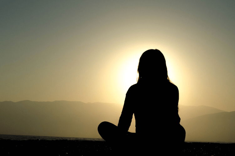 Woman meditating with sun behind head
