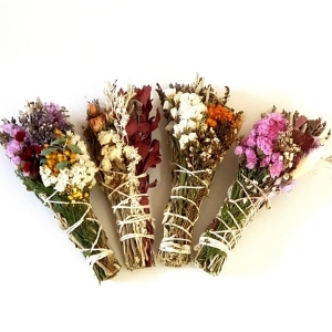 Mixed handmade floral smudge sticks on table