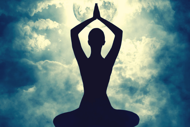 Women crossed legged with hands in prayer position above her head