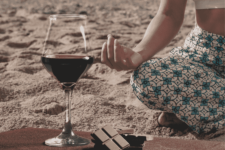 Women in meditation with glass of wine by hher side
