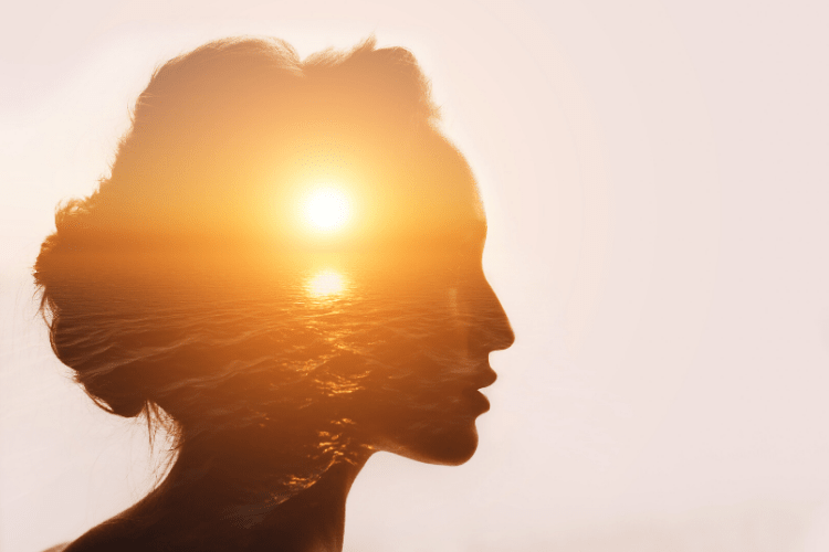 Silhouetteof a women with sunrise pasted over her head