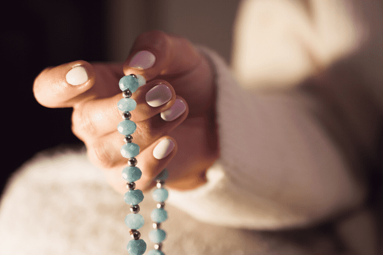 Women counting beads on a mala in her hand