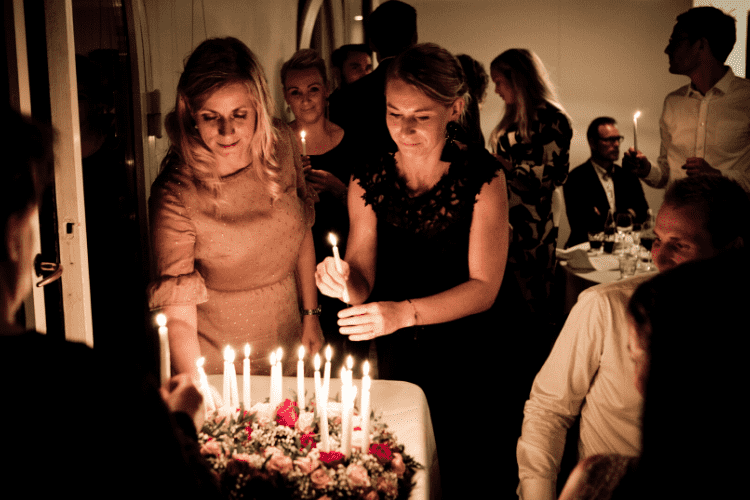 People lighting candles for a loved one at a funeral wake