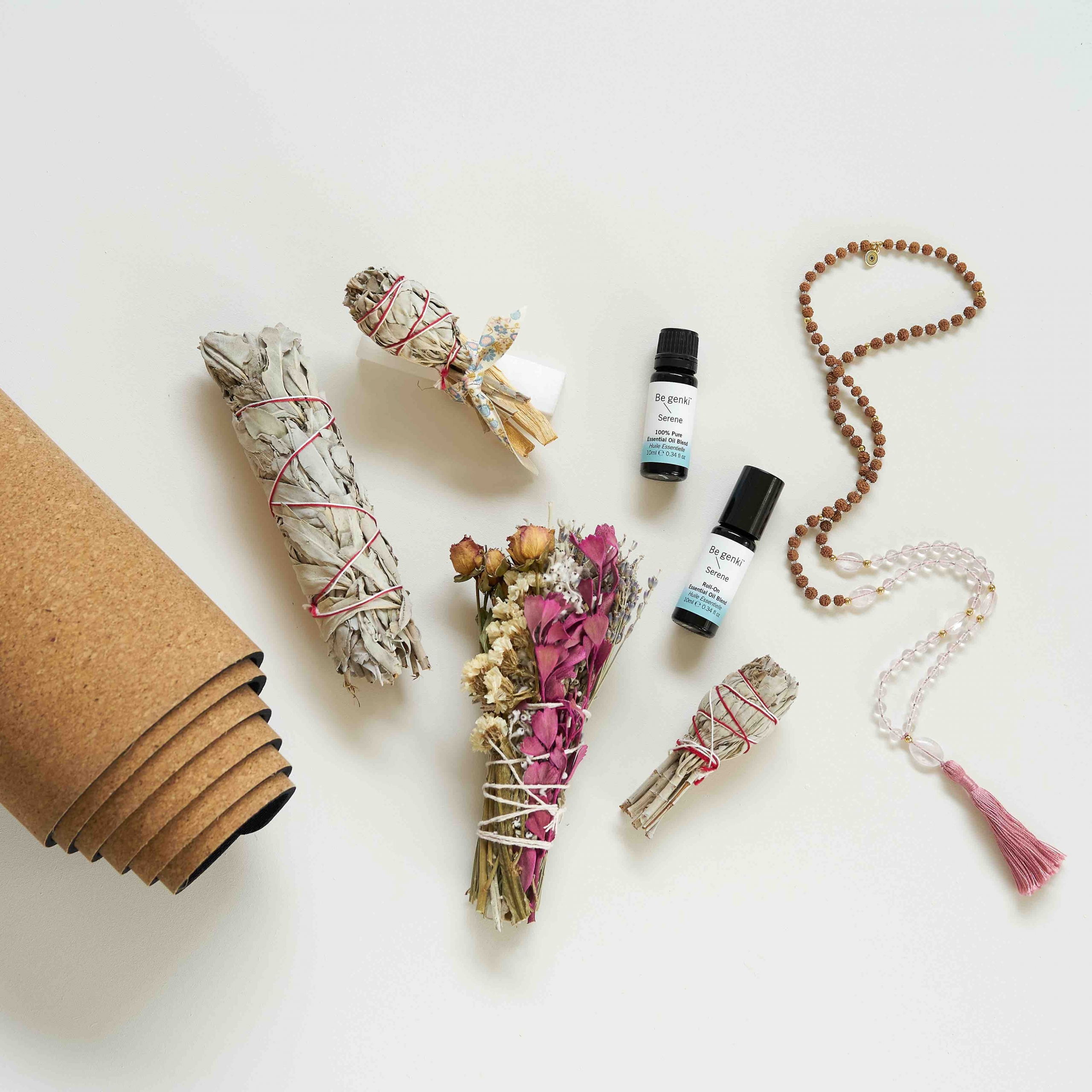 Smudging supplies, yoga mat, mala and essential oils on table