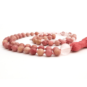 Handmade heart mala with Rhodochrosite and Rose Quartz curled on a table