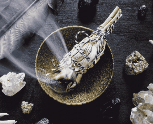Smudge stick smoking in brass ornate bowl surrounded by crystals and feather