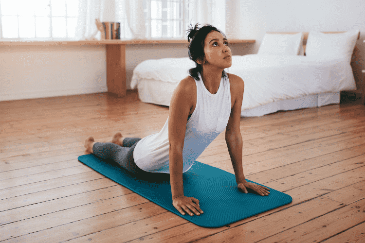 Woman pracicing yoga in her bedroom