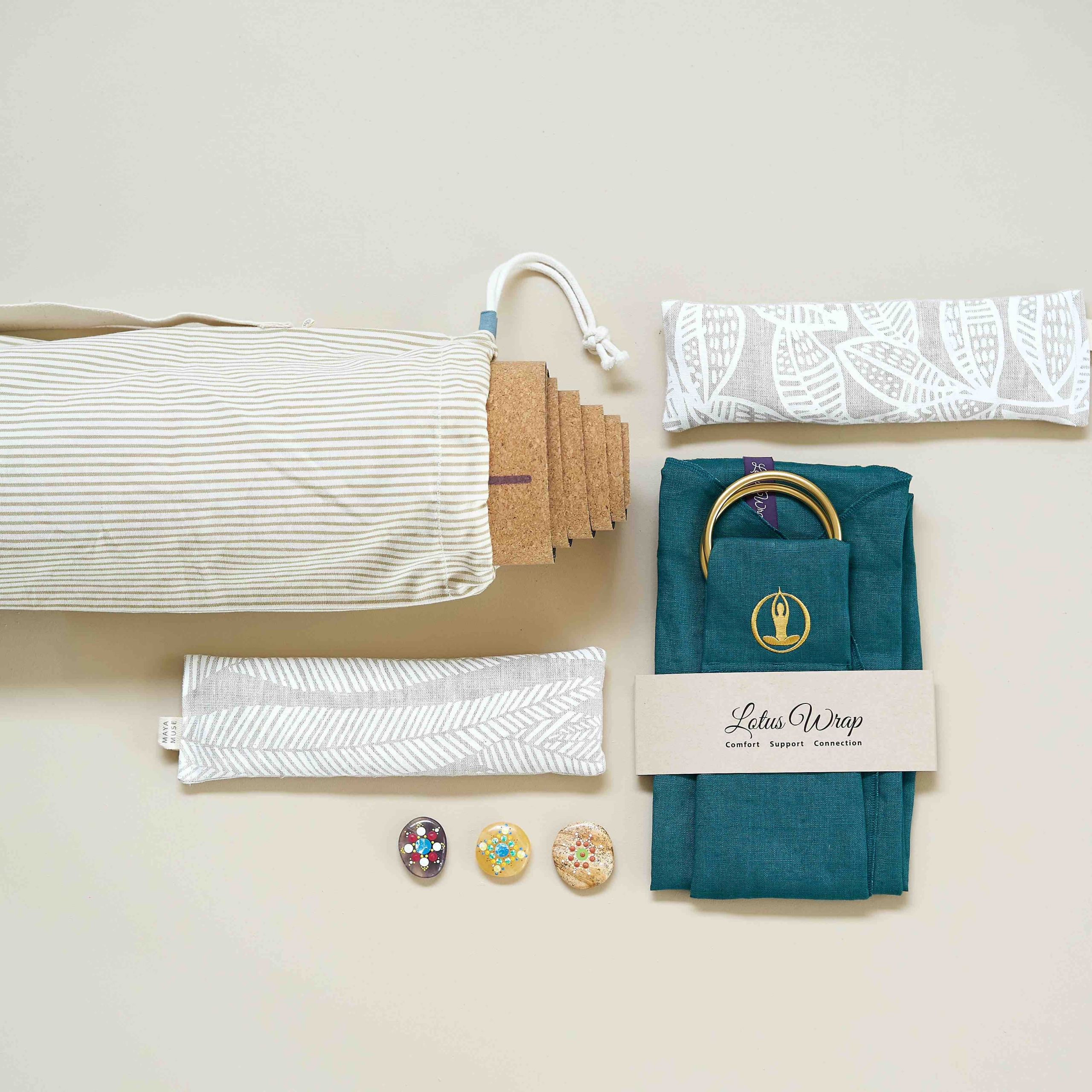 Yoga mat poking out of mat bag surrounded by an eye pillow, lotus meditation support wrap and shavasana stones