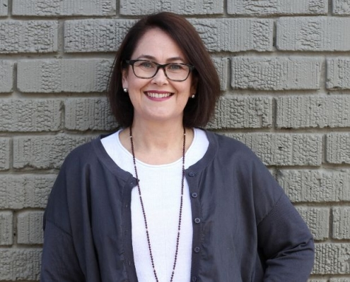 Tracey Francis from Essential Oils standing against brick wall